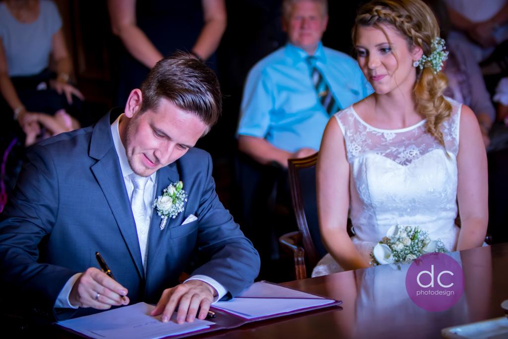 Hochzeitsfotografie - Bräutigam Unterzeichnung Heiratsurkunde im Standesamt Schloss Philippsruhe - Hochzeitsfotograf Hanau dc - photodesign
